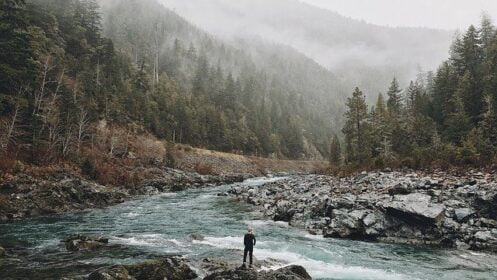 Why is mental strength important in survival, man in front of a river and a mountain